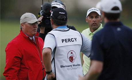 Rozhodčí John Mutch (vlevo), hráči a kedíci diskutují, zda je dost světla, aby play-off Justin Timberlake Shriners Hospitals for Children Open pokračovalo i na čtvrté jamce.