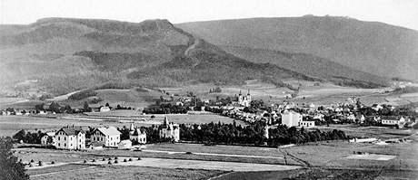 Víc než sto roků starý pohled na Hejnice od severu z pastvin tehdy zvaných Skřivánčí pole, z dnešního sídliště Na Skřivánku. Všechny čtyři domy vlevo dole dosud stojí. Nejvíc vlevo je hostinec U Smrku. Světlá stavba v lesíku je bývalá vodárenská věž.