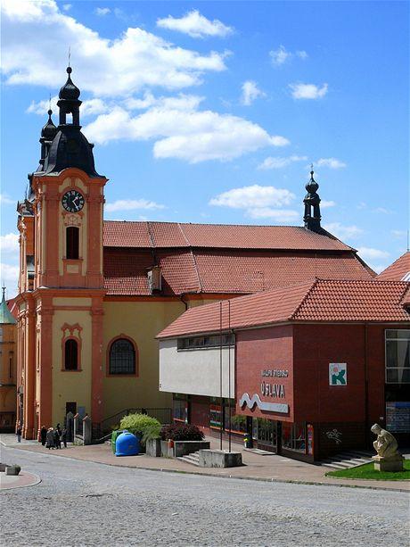 Nepomuk, kostel sv. Jana Nepomuckého zčásti zakrytý budovou nákupního střediska