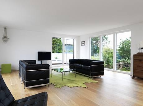 """Velký obývací pokoj v patře, na jeho konci je vstup na střešní terasu nad garáží. Z terasy je výhled nejen na moře, ale také na nedalekou dostihovou dráhu. Kožené pohovky od Le Corbusiera doplňuje stolek """"PK61"""". U stěny je televize od Bang&Olufsen."""