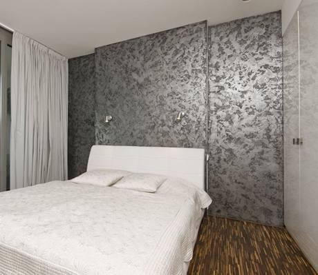 Stěna za čelem postele je ve stříbrné hlazené stěrkové omítce s kavernovitými strukturálními efekty Granite