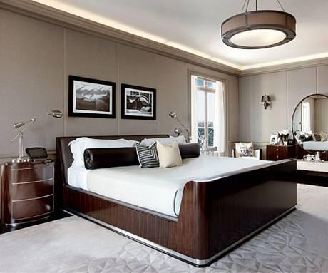 Ložnice majitele bytu. Tmavé exotické dřevo s leskem je jednotné u veškerého nábytku. Na zdi visí fotografie od Helmuta Newtona