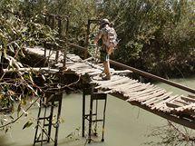 Skupina vojáků přechází po vratké lávce na druhou stranu řeky
