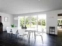 """Jídelna má přímý vstup na zahradu. Kolem elipsovitého stolu jsou židle od Arneho Jacobsena s názvem """"Sedmička"""". Stůl osvětlují dvě skulpturální lampy """"IQ-light"""", zahradní květiny i puntíkaté vázy ladí s černobílým interiérem."""