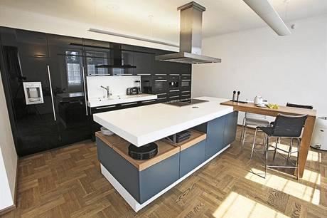 Luxusní kuchyň Poggenpohl Plusmodo – ostrůvek v matném laku v barvě aqua blue, otevřené výsuvy z jilmové dýhy a pracovní deska z 13 cm silného bílého corianu.
