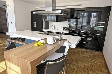Sestava vysokých skříní je lakovaná v černé barvě ve vysokém lesku. Kuchyně je vybavená spotřebiči Miele, Gaggenau a odsavačem par Gutmann.