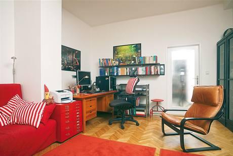 Tady vznikají originální počítačové grafiky. Hluboký pracovní stůl se přistěhoval z předchozího bytu, rozkládací pohovku pořídil pan Trojánek novou, samozřejmě v červené barvě.