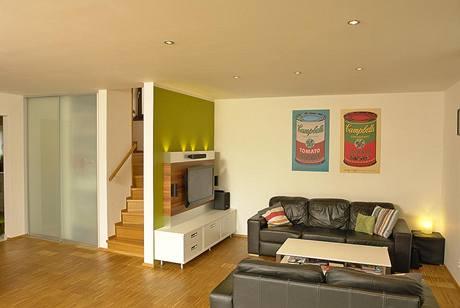 Schodiště do podkroví je integrováno do obývací části a odděleno polopříčkou, za posuvnými skleněnými dveřmi se ukrývá hrací kout pro děti
