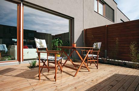 Dřevěnou terasu dělí od obývacího pokoje velká prosklená stěna