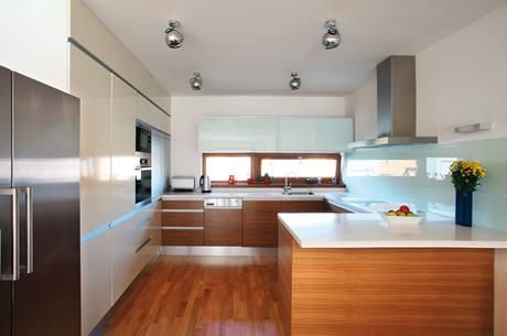 Kuchyň s povrchy z ořechové dýhya světlého polomatného laku. Desku tvoří umělý kámen Bienstone. Záda kuchyňské sestavy vpravo jsou z bílého lacobelu.