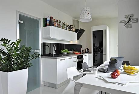Kuchyňská linka Ora-I;to (Gorenje) kombinuje černou a bílou stejně jako zbylý obývací prostor a svým leskem se doplňuje s litou podlahou