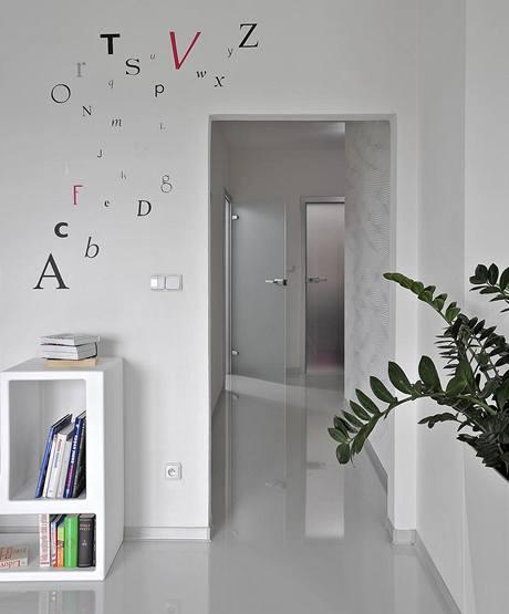 Lesklá podlaha vytváří zajímavý zrcadlový efekt. Bílé stěny jsou dekorovány tapetami (Lars Kontzen) a nálepkami ve tvaru písmen (Wise Decor)