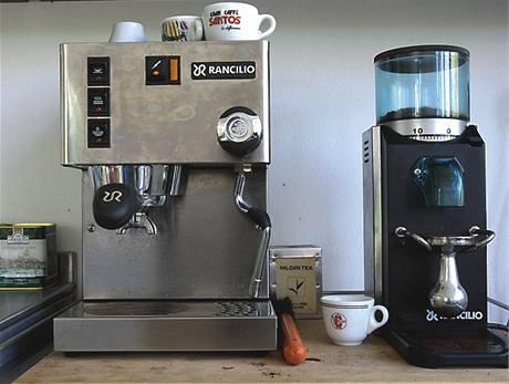 V rohu stojí profesionální kávovar a vedle mlýnek, stejný profesionál
