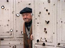 Starý obyvatel Vukovaru vykukuje z prostřílených vrat svého domu (1991)