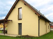 Členitější vzhled dodala domu dřevěná pergola, obíhající roh stavby a zastřešující terasu u obytné části přízemí