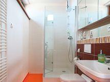 """Koupelna u ložnice kombinuje oranžovou podlahu a bílé i hnědé obklady s reliéfními """"vlnkami"""""""