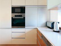 Dvě skříňky s roletami z hliníku slouží k ukládání nádobí i potravin. Všechny spotřebiče jsou značky Miele.