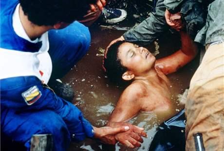 Záchranáři drží mrtvou Omayru Sanchezovou. Zemřela po více než šedesátihodinovém uvěznění ve vodě. (16. listopadu 1985)