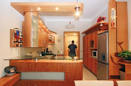 Kuchyňská linka s římsami, prosvětleným barem a dekorativní stěnou s kočičí intarzií, která kryje bok chladničky