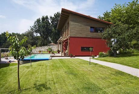 Jednoduchou hmotu domu s pultovou střechou v exteriéru obohacuje předsazená dřevěná pergola (v budoucnu vznikne v patře balkon) a obložení