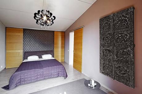 Ložnice vyniká efektní barevnou kombinací. Za čelem postele je vestavěna praktická šatna.