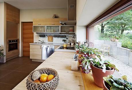 Na kuchyňskou linku s dvířky v březové dýze navazuje masivní jídelní stůl z teakového dřeva. Část pracovní plochy je přímo osvětlena východním horizontálním oknem.