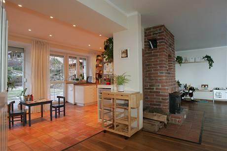 Obývací prostor v přízemí s cihlovým krbem je zároveň jídelnou a také dětskou hernou