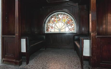 Výklenek pod schodištěm, takzvaný bay window, směřuje do zahrady. Okno zdobí vitráž s motivem květin