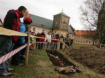 Skupinka zájemců u jedné ze sond v klášteře Teplá, kde je patrná cihlová zeď.