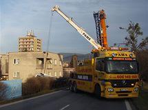 Vyprošťování kamionu s cisternou vážící 22 tun, který se převrátil na silnici z Třince do Frýdku-Místku. V pozadí je na horním rohu domu vidět poškození způsobené poraženým sloupem.