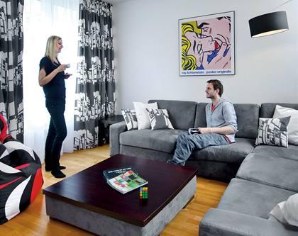 Přední část obývacího pokoje patří odpočinku. Designová svítidla ladí se závěsy i s polštářky, které designérka ušila na míru z látky IKEA