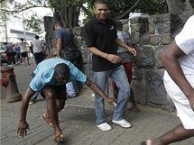 Lidé utíkají před střelbou v ulicích jedné z favel brazilského Ria de Janeira ukazuje cestu hasičům