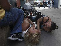 Lidé se skrývají před střelbou v ulicích brazilského Ria de Janeira ukazuje cestu hasičům
