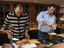 Chorvatský šéfkuchař připravuje spodní vrstvu upečeného listového těsta do misky, italský mu míchá krém