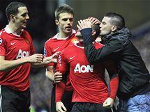 NE�EKAN� GRATULANT. �to�n�k Wayne Rooney z Manchesteru United (t�et� zleva) slav� g�l v utk�n� Ligy mistr� proti Glasgow Rangers. P�i tom se na n�j vrhl jeden z fanou�k�.