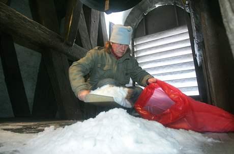 Správce Jan Vančura musí sníh shrnout a lopatkou nandat do pytle.