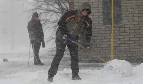 Obyvatelé Staměřic na Přerovsku uklízejí sníh i přes silný vítr a husté sněžení.
