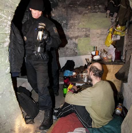 Strážníci kontrolují bezdomovce v Praze.