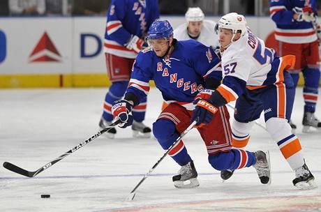 K��deln�k Rangers Mari�n G�bor�k (vlevo) unik� v newyorsk�m derby. st�h� ho Blake Comeau z t�mu Islanders.