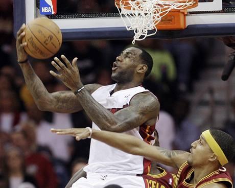 LeBron James (v b�l�m) z Miami Heat zakon�uje p�es atak Jamaria Moona z Clevelandu Cavaliers
