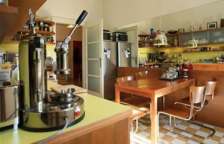 Moderní je žlutohnědá kuchyňská linka, která však nijak nevraží na dobové trubkové židle Breuer a prostý dřevěný stůl