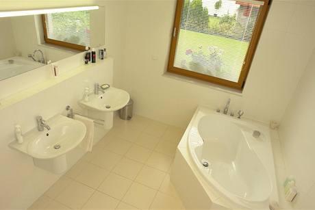Rodinnou koupelnu charakterizují odstíny bílé, sklo a chrom