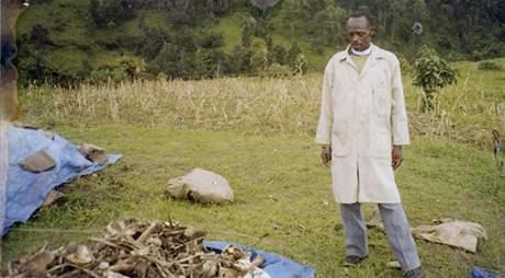 Muž stojí nad ostatky obětí ve rwandském Biseseru.