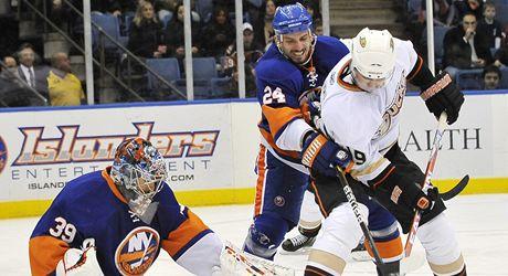 Obr�nce New Yorku Islanders Radek Mart�nek (uprostøed) se sna�� vyèistit prostor pøed sv�m brank�øem Rickem DiPietrem, do �ance se tlaè� Joffrey Lupul z Anaheimu.