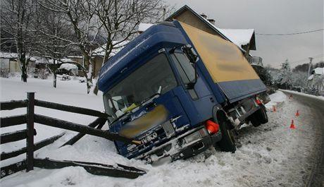 Řidič nákladního auta se vyhýbal dalšímu vozu, který ho omezil v jeho jízdním pruhu, a zasněžená krajnice ho jeho auto neunesla.
