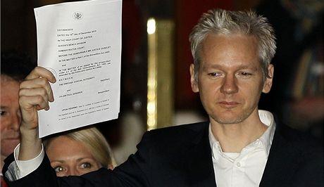 Zakladatel serveru WikiLeaks Julian Assange ukazuje dokumenty o svém propuštění (16. prosince 2010)