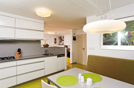Průhled z kuchyně do obývacího pokoje: nad plynovým vařičem Mora je výsuvná digestoř Miele, vpravo pak vestavná myčka Bosch.