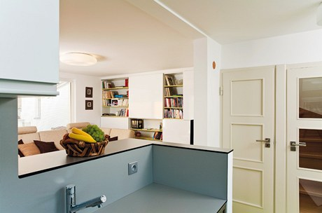 Probourání stěny mezi obývacím pokojem a kuchyní prostor zvětšilo. Dělení obstarává kuchyňský pult.