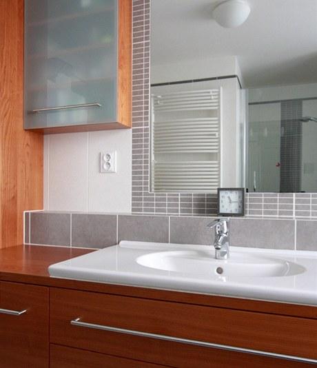 V koupelně je nábytek z lakované třešně
