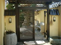 Dřevěná vstupní brána pochází z Japonska. Před branou jsou po obou stranách nezbytné očistné studánky
